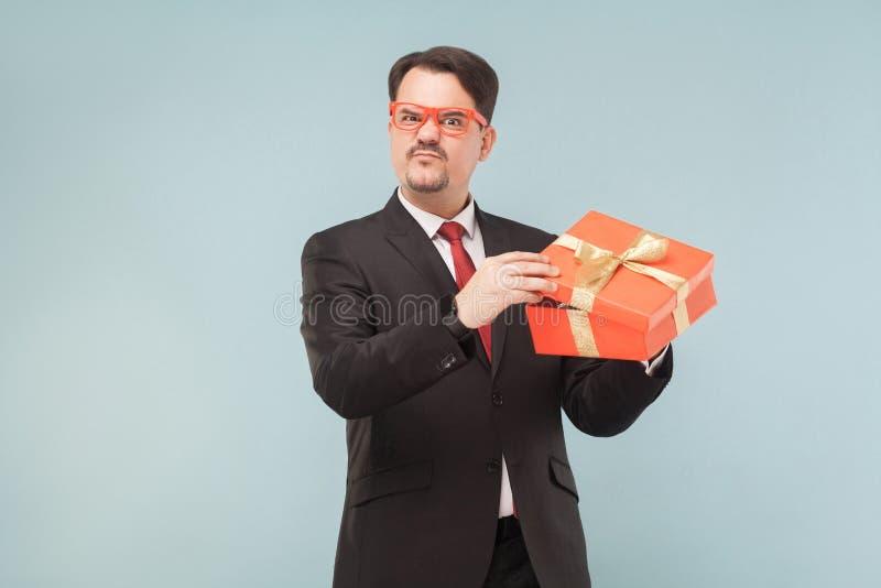 嘿!它` s我的礼物!拿着礼物盒的严肃贪婪人 库存照片