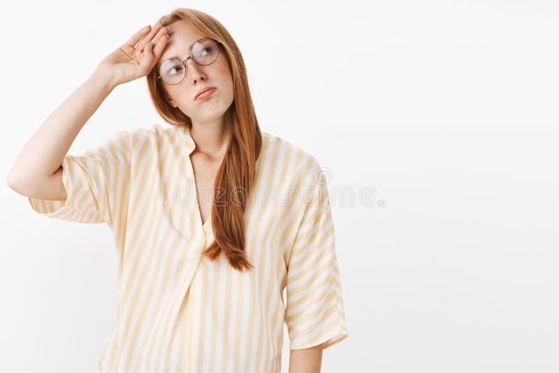 噗最后被完成的工作 疲乏的unemotive阴沉的红头发人女孩画象有雀斑的在玻璃和黄色女衬衫 免版税库存图片