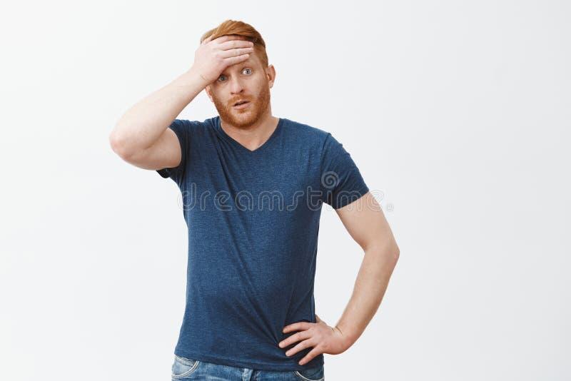 噗,几乎捉住 逗人喜爱的疲乏的人,在前额外面的whiping的汗水画象有被解除的红色头发feelling的,注视 免版税图库摄影