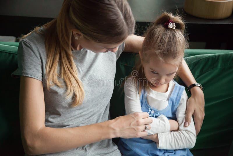 噘嘴阴沉的恼怒的被触犯的孩子的女孩忽略责骂h的母亲 免版税图库摄影