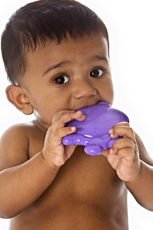 嚼印第安甜玩具的婴孩 免版税库存照片