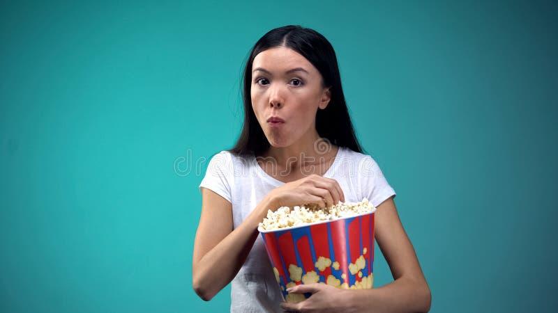 嚼玉米花和观看在戏院,概念的被集中的妇女令人激动的影片 免版税库存图片