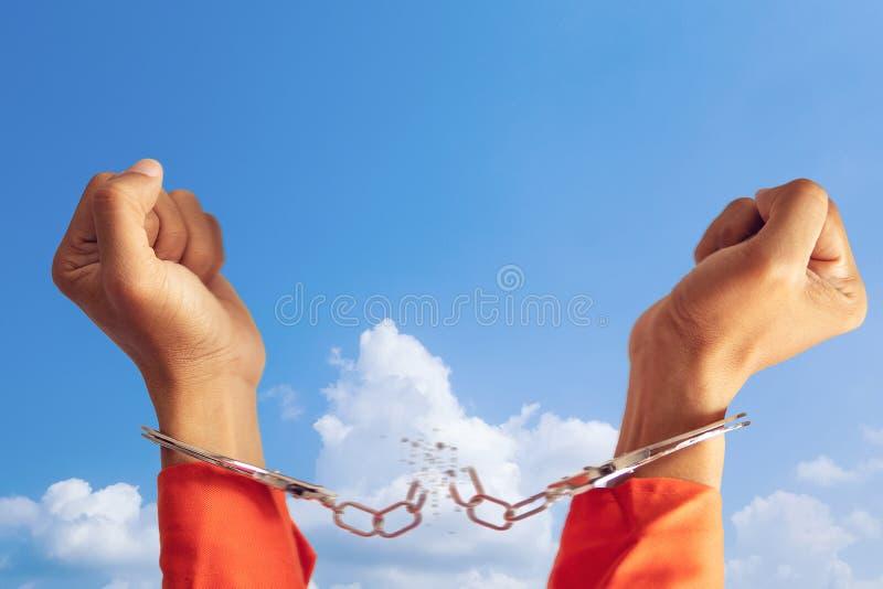 囚犯的两只手有残破的手铐的意味与天空蔚蓝的自由的在背景 图库摄影