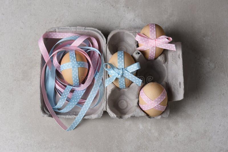 四丝带装饰了在纸盒的鸡蛋 库存照片