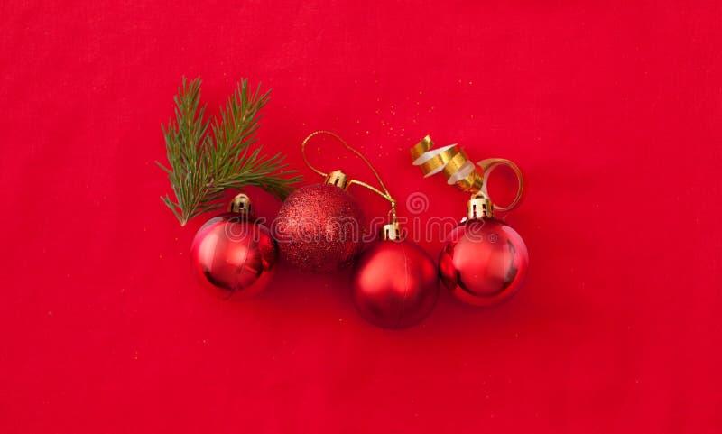 四个不同红色圣诞节球连续在红色 免版税库存照片