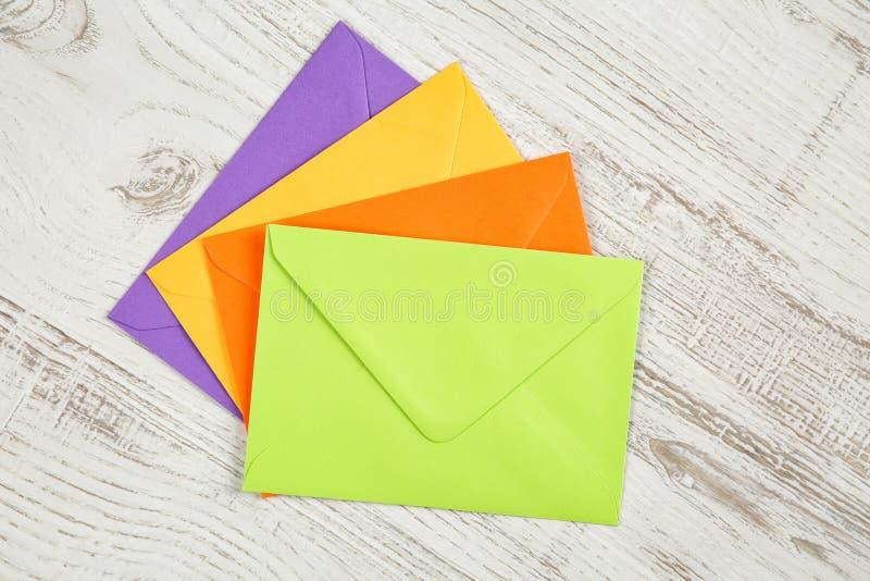 四个五颜六色的被密封的信封顶视图从被回收的纸的在一张白色土气木桌上 免版税图库摄影