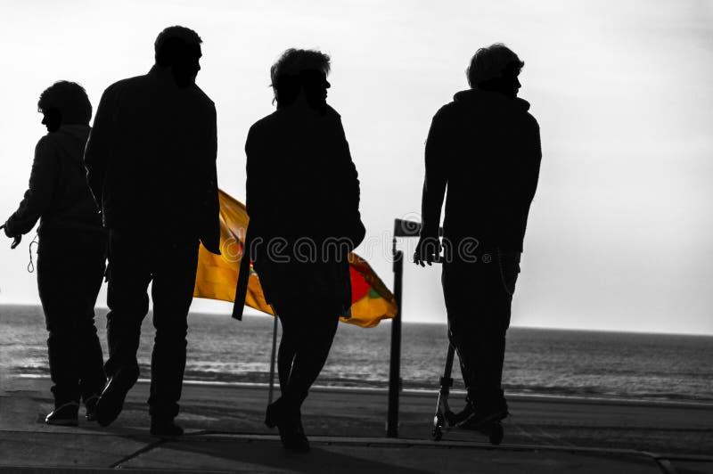 四个人剪影在海岸附近的 库存照片