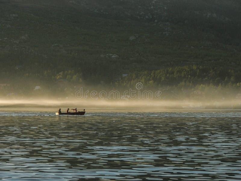 四个人剪影独木舟的有在森林backgroun的桨的 免版税库存图片