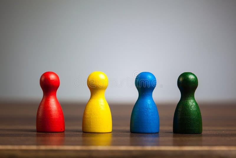四个典当小雕象,队概念,桌,灰色背景 免版税库存图片