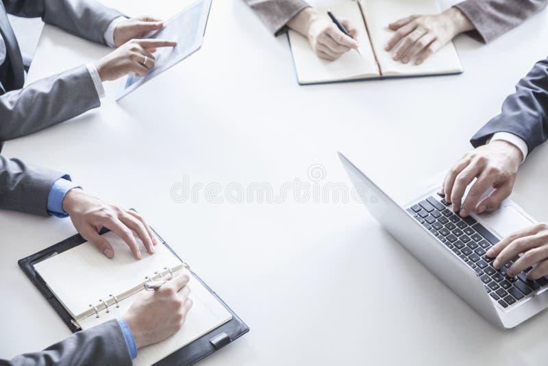 四个商人在桌附近和在业务会议,仅手期间 库存图片
