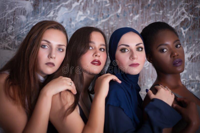 四个女孩画象有另外肤色和国籍的在演播室 免版税库存图片