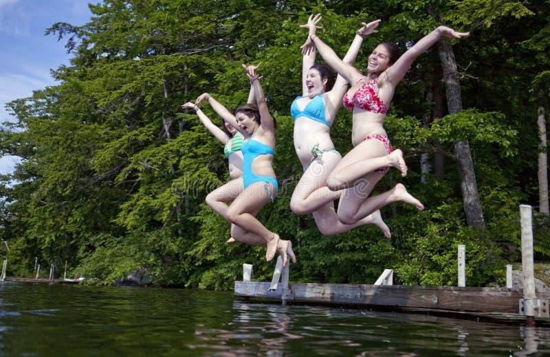四个少年女孩愉快的跳的湖 免版税库存图片