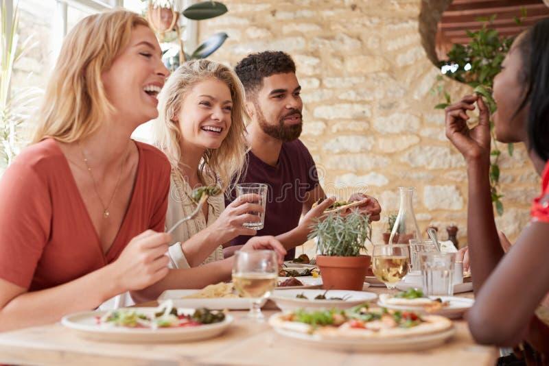 四个年轻成人朋友吃光在餐馆的,关闭 库存图片