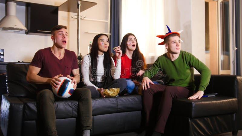 四个年轻朋友坐沙发和观看的足球赛佩带的俄国属性 库存照片