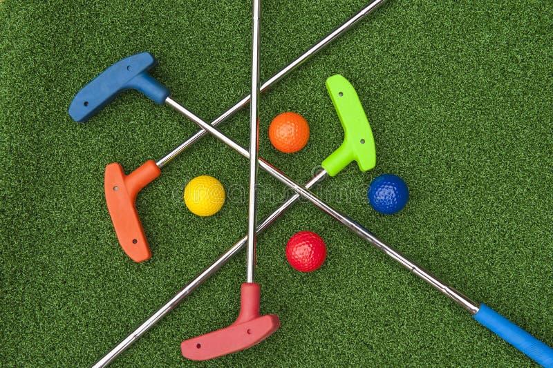 四个微型高尔夫球轻击棒和球 免版税库存图片