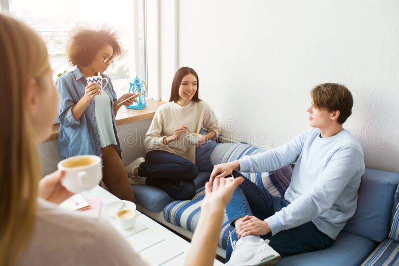 四个朋友一起被会集 他们互相谈话并且获得一些乐趣 学生有一个断裂 冒犯 图库摄影