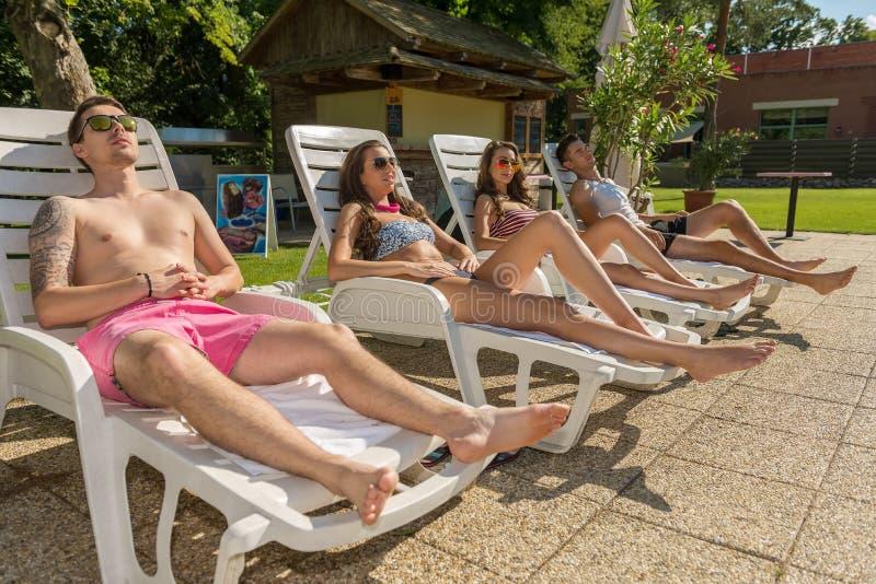 四个朋友在海滩的太阳懒人晒日光浴 库存照片