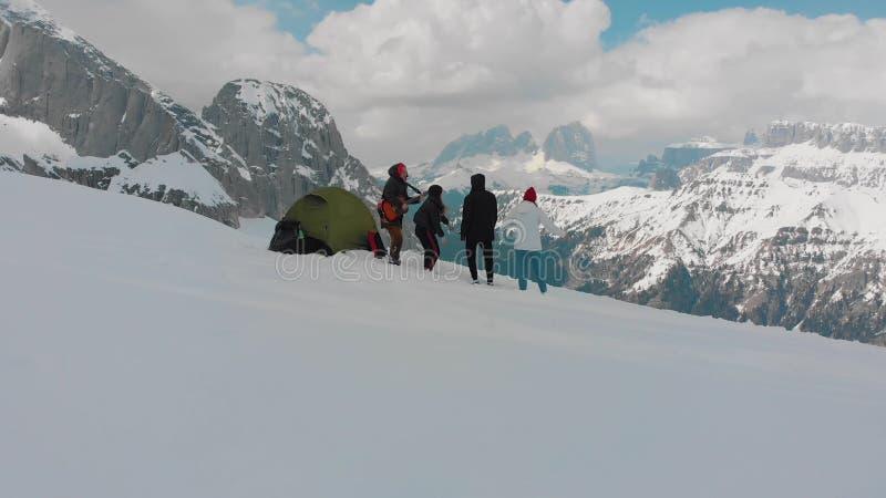 四个朋友设置了在一个山和身分在-弹吉他的一个人-白云岩之外,意大利的一个帐篷 免版税库存图片