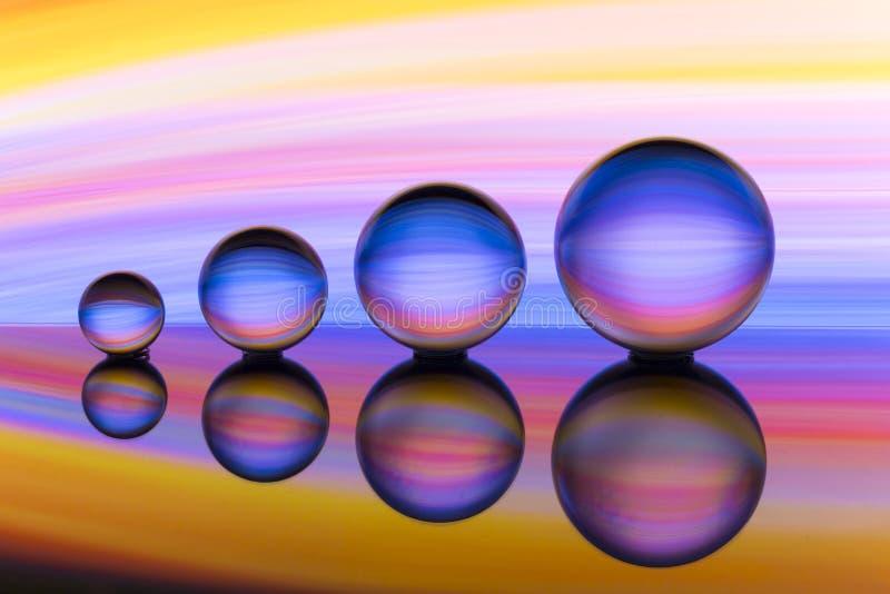 四个水晶球连续与彩虹颜色五颜六色的条纹在他们后的 免版税库存图片