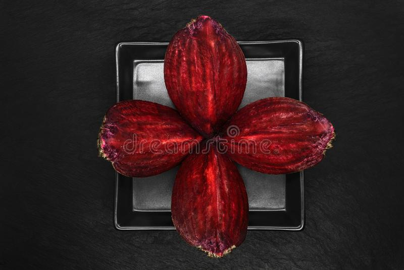 四个片断的抽象构成砍了在黑色的盘子和黑石背景安置的甜菜根 库存图片