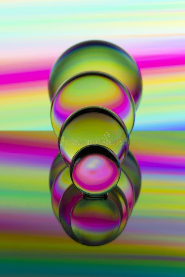 四个玻璃水晶球连续与五颜六色的轻的绘画彩虹在他们后的 图库摄影