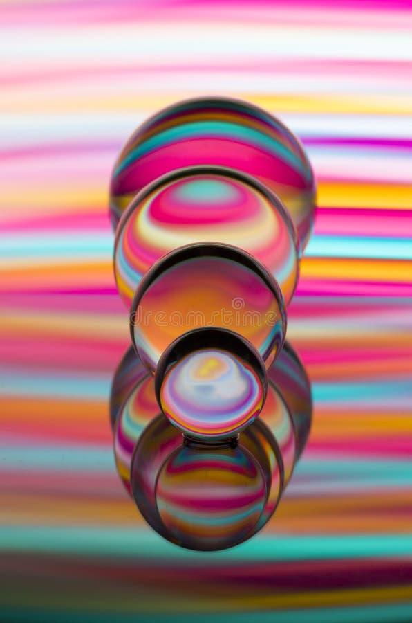 四个玻璃水晶球连续与五颜六色的轻的绘画彩虹在他们后的 库存图片