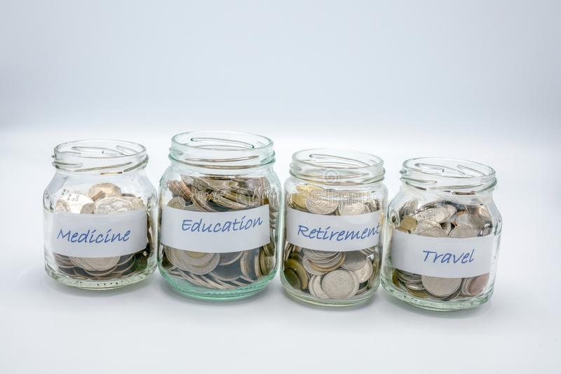 四个玻璃瓶用与医学,教育,退休,旅行商标纸的硬币填装了  免版税库存图片