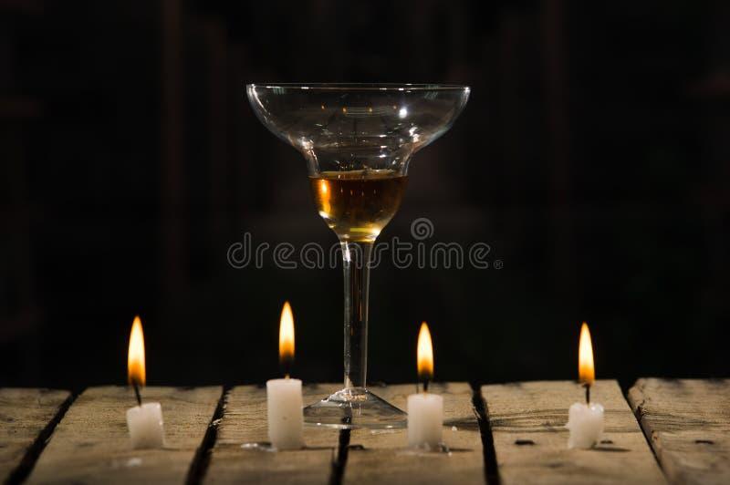 四个白色蜡蜡烛坐木表面燃烧,被安置的鸡尾酒杯后边,黑背景 免版税库存照片