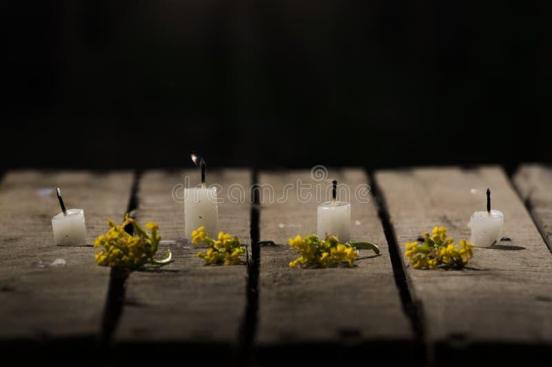 四个白色蜡蜡烛坐木表面,没有烧,有黑背景,美好的轻的设置的火焰 库存图片