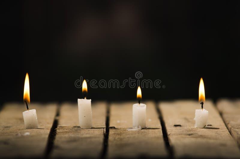 四个白色蜡蜡烛坐烧有黑背景,美好的轻的设置的木表面 免版税图库摄影