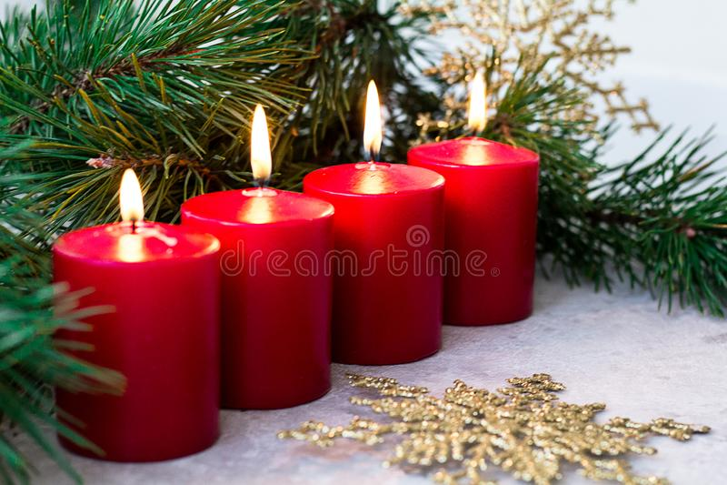 四个红色灼烧的出现蜡烛和冷杉在轻的背景分支 库存图片