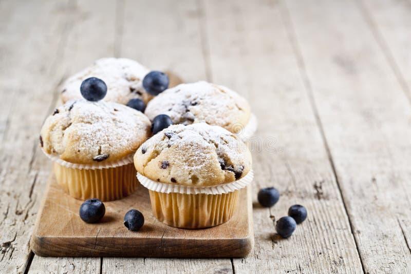 四个自创新鲜的松饼用在土气木桌背景的蓝莓 图库摄影