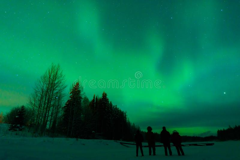 四人有看北极光极光Borealis Kuukiuru村庄湖在拉普兰,芬兰 免版税库存图片
