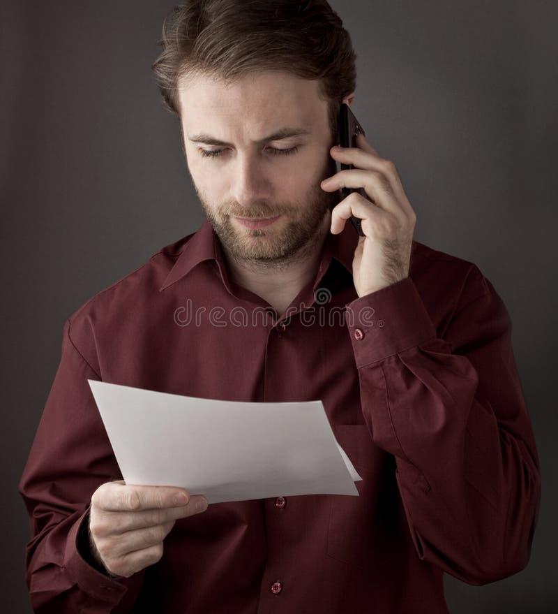 读纸张文件的办公室工作者在移动电话交谈时 免版税库存图片