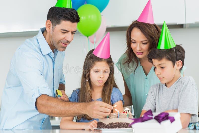 四口之家与在生日聚会的蛋糕 免版税库存照片