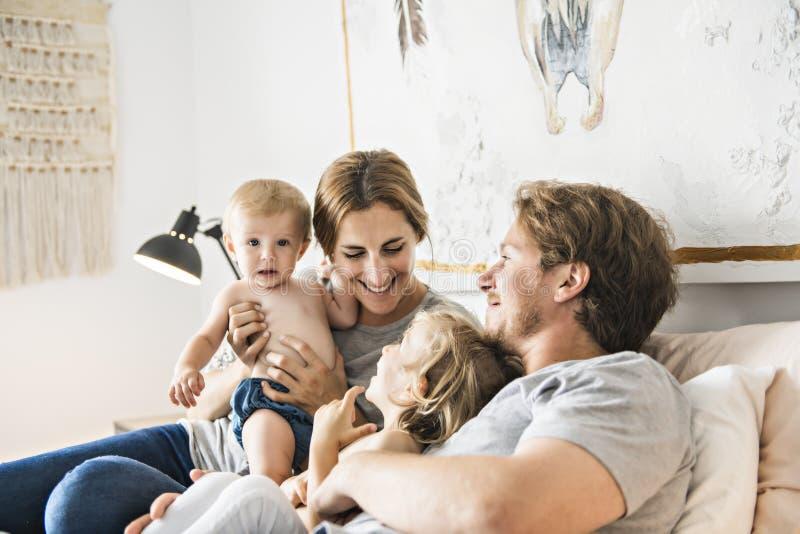 四口之家与获得的婴孩在床上的乐趣 免版税图库摄影