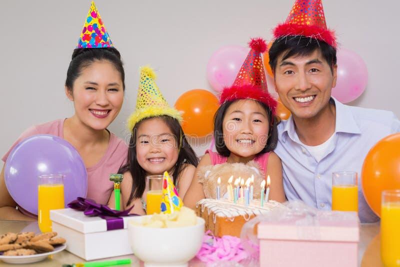 四口之家与蛋糕和礼物在生日聚会 免版税库存照片
