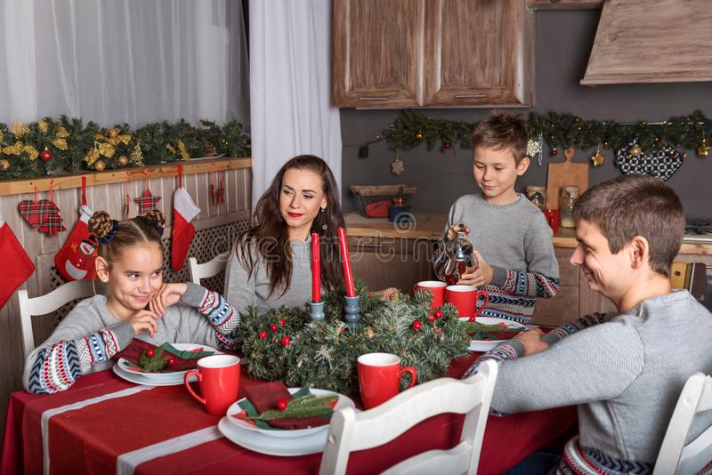 四口之家在相同毛线衣坐在圣诞节桌上,并且男孩在新年的装饰的厨房里倒茶 免版税库存图片