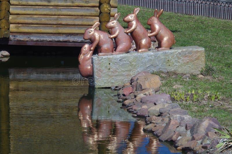 四只兔子抢救概念性雕塑在水外面的另一只兔子 免版税库存照片