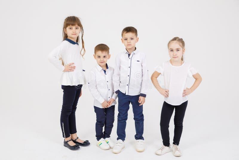 四可爱,俏丽的孩子-男孩和女孩在白色背景站立,隔绝 免版税库存照片