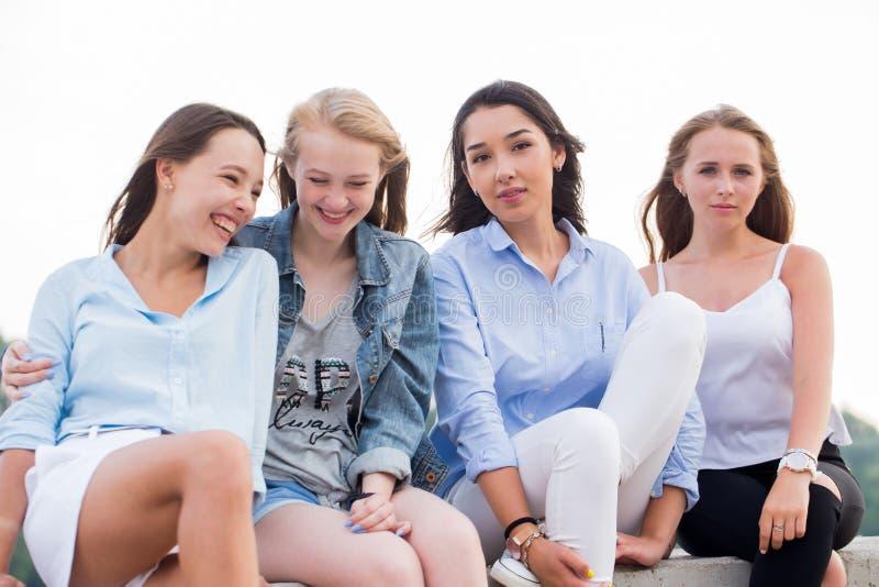 四名可爱的妇女在夏天给坐穿衣在具体边界靠近河在studing以后在学院 免版税库存图片