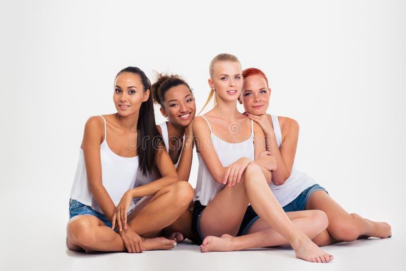 四名妇女坐地板 免版税库存图片