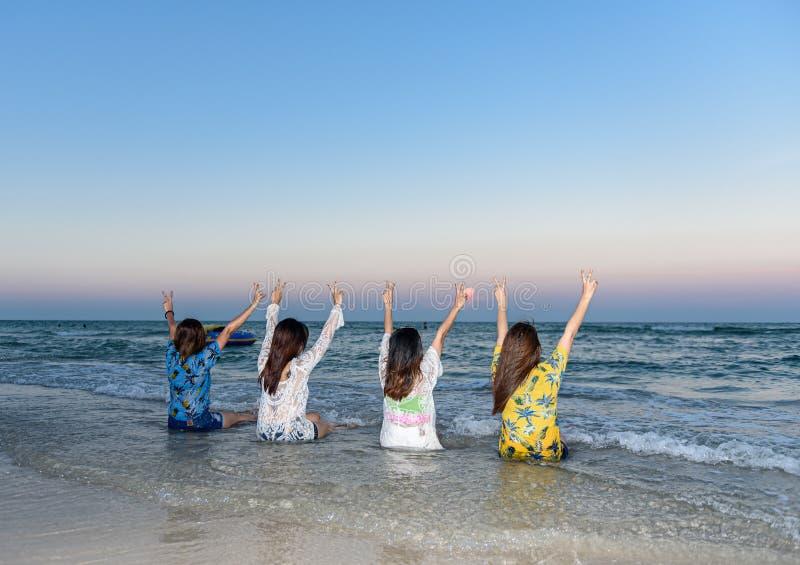 四名妇女是朋友,松劲并且举了他们的在海滩的手 库存照片
