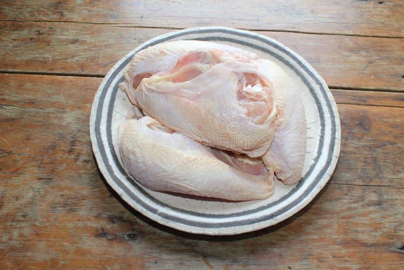 四在一块板材的未加工的分裂鸡胸脯在桌上 免版税库存照片