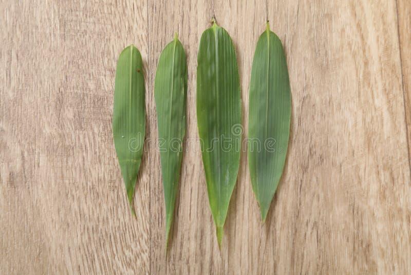 四在木桌上的绿色bambou叶子 免版税库存照片