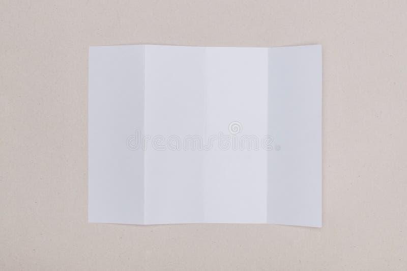 四在灰色背景的折叠白色模板纸 库存图片