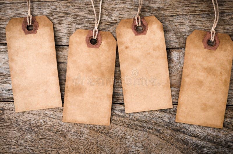 四垂直葡萄酒在木头的纸标签 免版税库存照片
