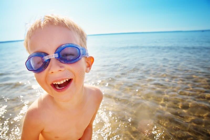 四岁使用在与游泳的玻璃的海滩的男孩 库存照片