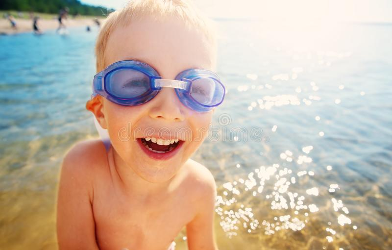 四岁使用在与游泳的玻璃的海滩的男孩 免版税库存图片