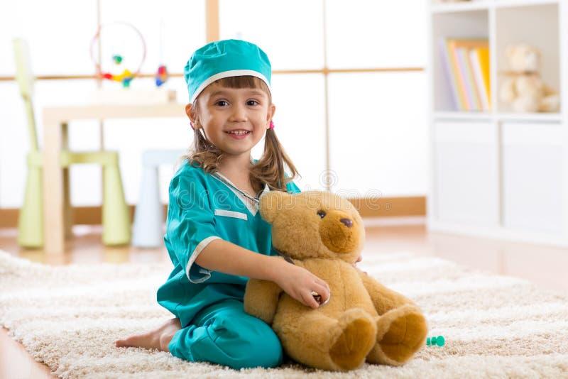 四岁扮演有长毛绒玩具的女孩医生在托儿所 库存照片